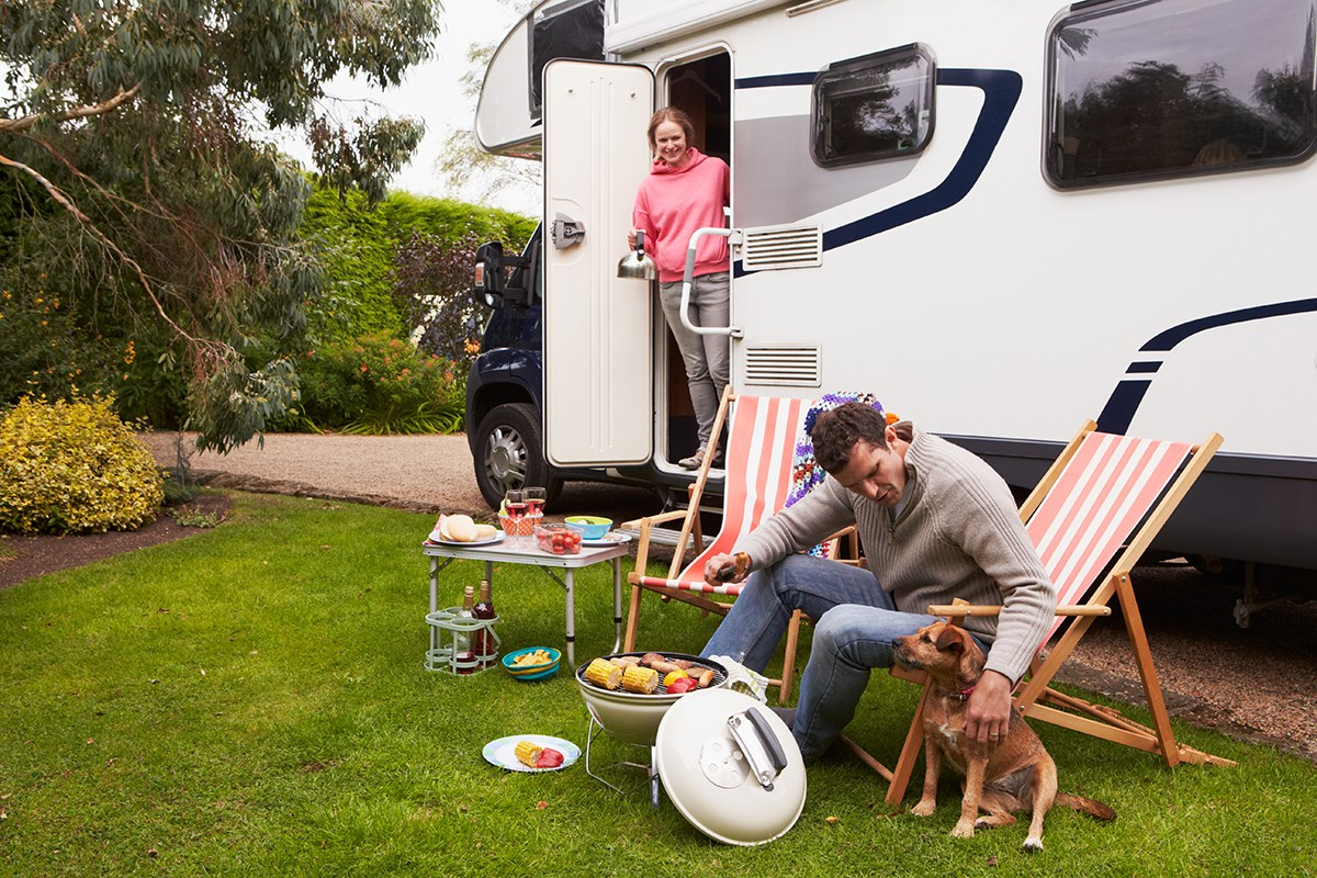 Un couple devant un camping-car au barbecue.